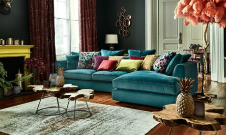 Large blue fabric sofa with bright cushions from Fishpools